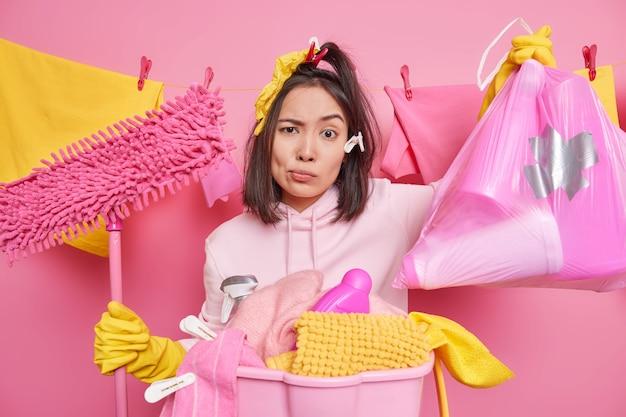 Ernstige ontevredenheid brunette aziatische vrouw draagt vuilniszak en dweil poses in wasruimte in de buurt van waslijn draagt sweatshirt beschermende rubberen handschoenen roze muur