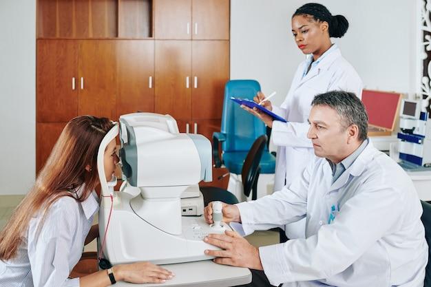 Ernstige oogarts die het gezichtsvermogen van de vrouw controleert wanneer de assistent medisch document vult