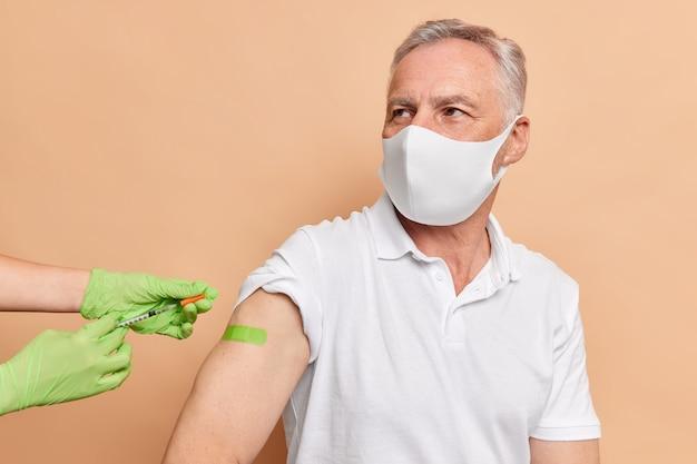 Ernstige oude man krijgt vaccinatie tegen coronavirus draagt beschermend wegwerpmasker groen plakband op arm gekleed in wit t-shirt poseert in de buurt van verpleegster die spuit vasthoudt
