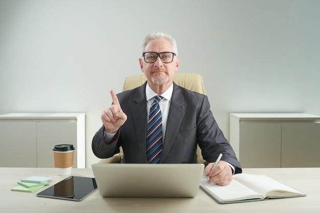 Ernstige oude ondernemer poseren voor fotografie