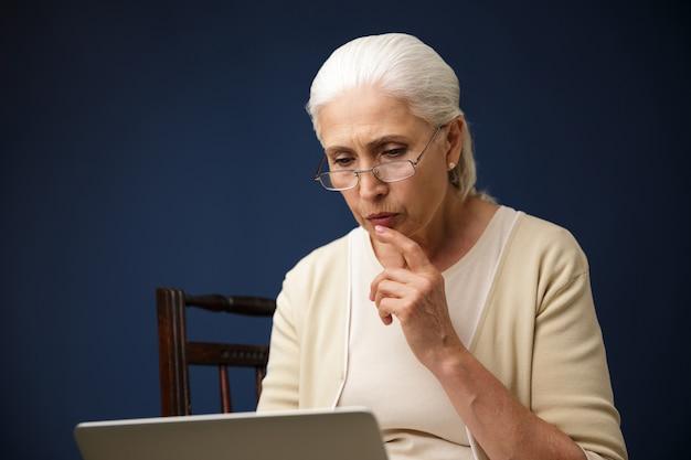 Ernstige oude vrouw die laptop computer met behulp van. opzij kijken.