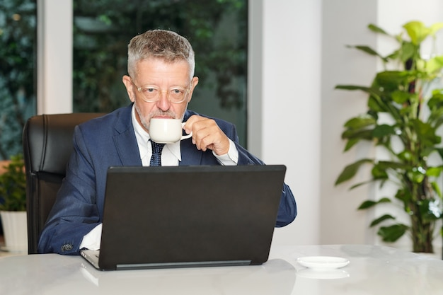 Ernstige oude zakenman ochtend espresso drinken en nieuws lezen op laptop scherm in café