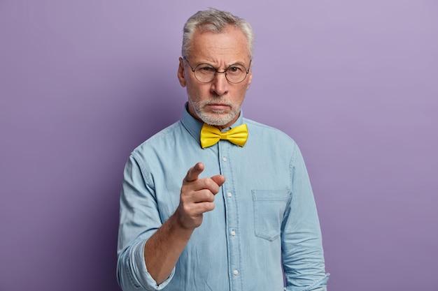 Ernstige oudere man in elegant overhemd met gele vlinderdas, ontevreden over onproductief werk van collega's