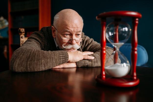 Ernstige oudere man kijkt op zandloper in thuiskantoor, de tijd kan niet worden teruggedraaid. rijpe oudste die op zandloper kijkt