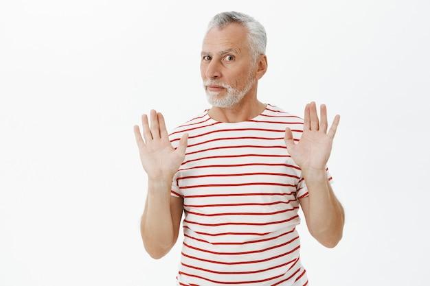 Ernstige oudere man verbiedt iets, het opheffen van de handen in stop, afwijzingsgebaar