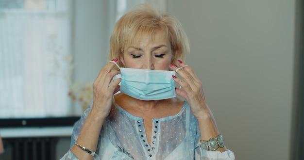 Ernstige oudere vrouw die chirurgisch masker aanbrengt dat tegen epidemische uitbraak beschermt.