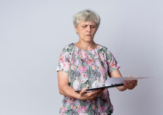 Ernstige oudere vrouw houdt en kijkt naar klembord geïsoleerd op een witte muur