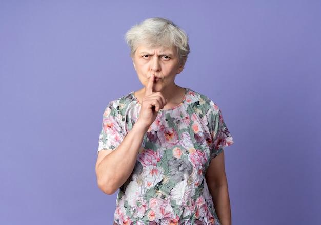 Ernstige oudere vrouw legt vinger op mond gebaren stil stil teken geïsoleerd op paarse muur