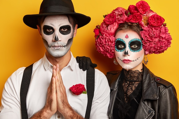 Ernstige paarzombie houdt de handpalmen tegen elkaar gedrukt, gekleed in zwart kostuum voor halloween