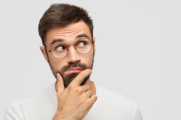 Ernstige peinzende bebaarde man met dikke stoppels, houdt kin vast en kijkt peinzend opzij, overweegt iets terwijl gefocust op de rechterbovenhoek