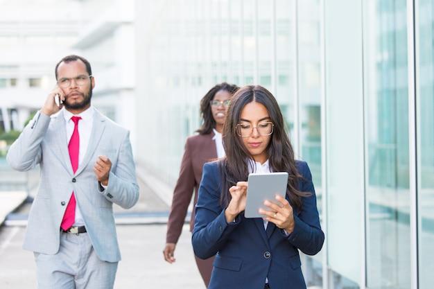 Ernstige peinzende bedrijfsvrouw die tablet gebruiken terwijl het lopen