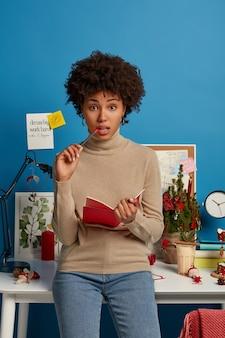 Ernstige peinzende, gekrulde vrouwelijke studenten schrijven opstel in leerboek, bezig met onderwijs en autodidact, maken aantekeningen in kladblok, poseert bij desktop in studeerkamer, maken huiswerk, nonchalant gekleed.
