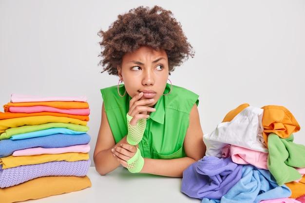 Ernstige peinzende jonge afro-amerikaanse vrouw gefocust weg omdat ze diep in gedachten is, maakt planning voor weekenden aan tafel met stapels kleding vouwen wasserij thuis geïsoleerd over wit