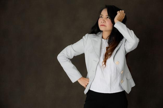 Ernstige peinzende jonge aziatische zakenvrouw in stijlvolle outfit die het voorhoofd aanraakt en bedachtzaam wegkijkt tegen een donkergrijze achtergrond met lege ruimte