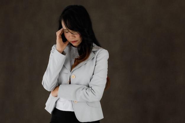 Ernstige peinzende jonge aziatische zakenvrouw in stijlvolle outfit die het voorhoofd aanraakt en de ogen zorgvuldig sluit tegen een donkergrijze achtergrond met lege ruimte
