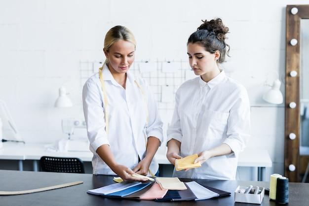 Ernstige peinzende jonge vrouwen in witte overhemden die textiel bespreken voor het naaien in de werkplaats