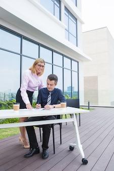 Ernstige peinzende mannelijke directeur die documenten ondertekenen die door secretaresse worden gegeven.