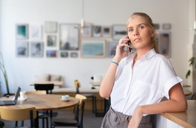 Ernstige peinzende mooie jonge vrouw, gekleed in een wit overhemd, praten over de mobiele telefoon, staande in co-werkruimte