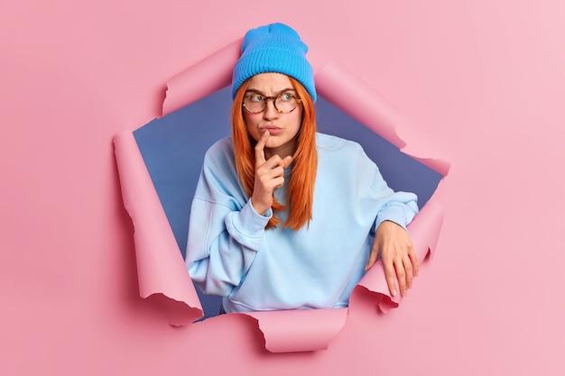 Ernstige peinzende roodharige jonge vrouw kijkt weg met doordachte geconcentreerde gezichtsuitdrukking houdt wijsvinger bij de lippen draagt blauwe kleding.