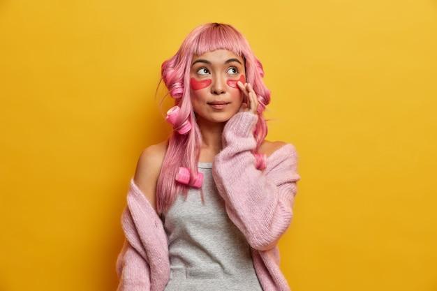 Ernstige peinzende roze harige aziatische vrouw met krulspelden op het hoofd, raakt patches voor een gezonde zachte huid