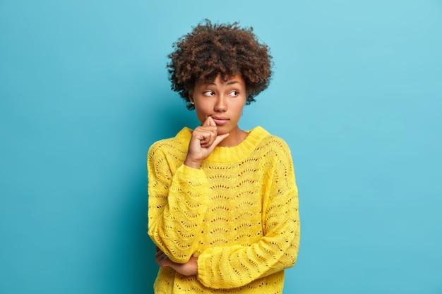 Ernstige peinzende vrouw met afro-haar kijkt weg en staat in een doordachte houding, denkt na over problemen en moeilijkheden gekleed in warme gele trui geïsoleerd op blauwe muur, neemt een besluit