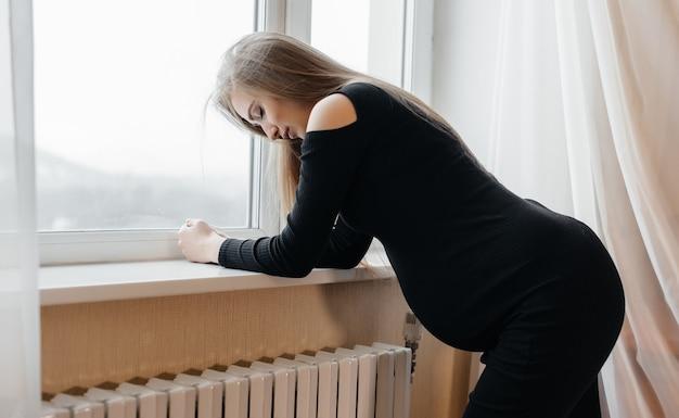 Ernstige pijn bij een zwangere vrouw die zich bij het raam bevindt. zwangerschap
