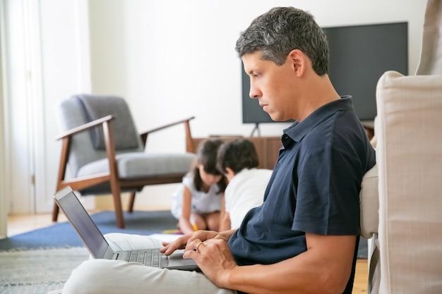Ernstige professional die thuis werkt, op de vloer zit en laptop gebruikt