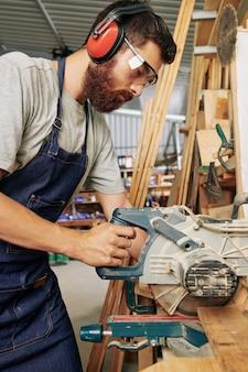 Ernstige professionele timmerman in oorwarmers die houten plank snijden met cirkelzaag