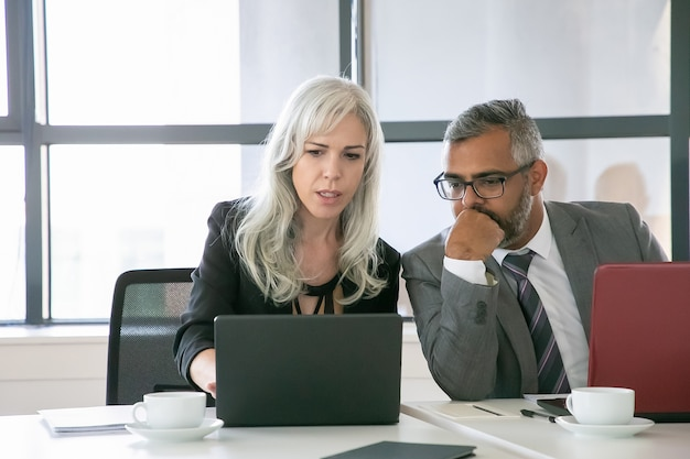 Ernstige projectmanager presentatie op laptop tonen aan collega of baas op kantoor. medium shot, vooraanzicht. teamwork en communicatieconcept