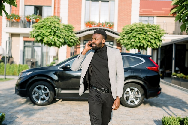 Ernstige rijke afrikaanse zakenman in slimme casual pak praten over de telefoon tijdens het wandelen op het erf en parkeren van moderne zakencentrum. zwarte auto-crossover.