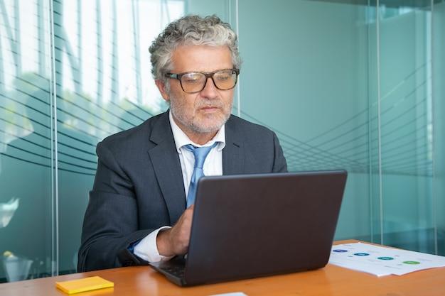 Ernstige rijpe uitvoerende die kostuum en glazen draagt, bij computer in bureau werkt, laptop aan lijst met behulp van
