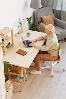 Ernstige rijpe vrouw aan de tafel zitten en online werken op laptop in de huiskamer