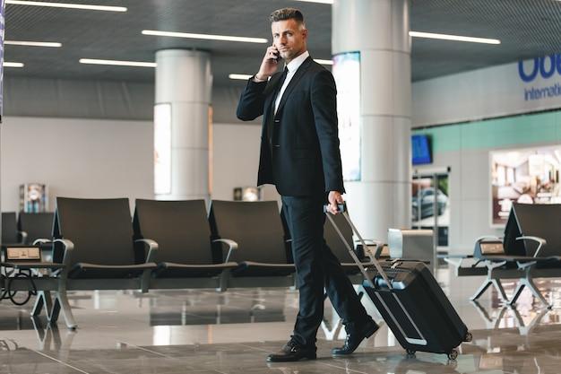 Ernstige rijpe zakenman die op mobiele telefoon spreekt