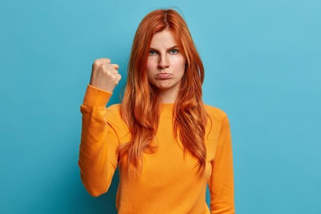 Ernstige roodharige europese vrouw kijkt boos toont vuist vraagt haar lippen niet lastig te vallen en heeft geïrriteerde gezichtsuitdrukking gekleed in een casual oranje trui.