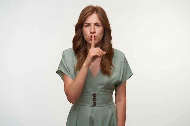 Ernstige roodharige jonge vrouw in romantische jurk op zoek met opgeheven wijsvinger naar haar mond, stil gebaar maken