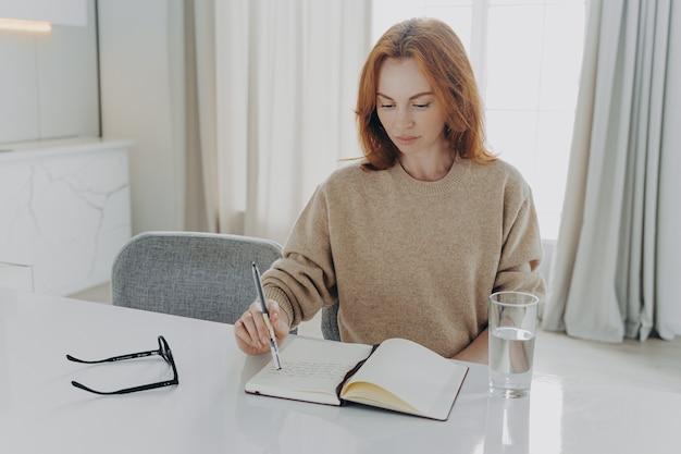 Ernstige roodharige jonge vrouw maakt aantekeningen in kladblok zit aan tafel