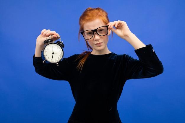Ernstige roodharige tiener meisje in glazen in een zwarte jurk houdt een wekker en vraagt om niet te laat te zijn blauw