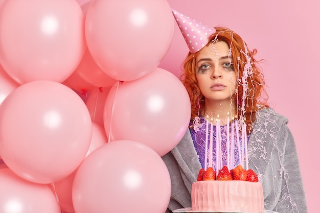 Ernstige roodharige vrouw met gelekte make-up kijkt recht naar voren draagt feestkegelvormige hoed kamerjas houdt heerlijke aardbeientaart vast en opgeblazen ballonnen vormen tegen roze muur