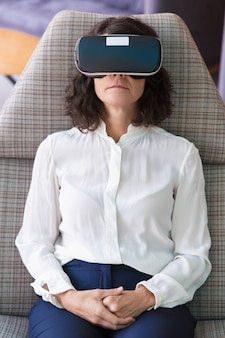 Ernstige rustige zakenvrouw kijken naar virtuele inhoud