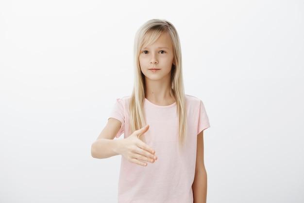 Ernstige schattige blonde vrouw steekt haar hand uit voor een handdruk, stelt zichzelf beleefd voor