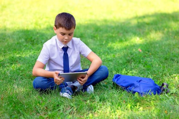 Ernstige schooljongen in een wit overhemd en blauwe stropdas zit op groen gras en speelt met een tablet. kopieer ruimte.