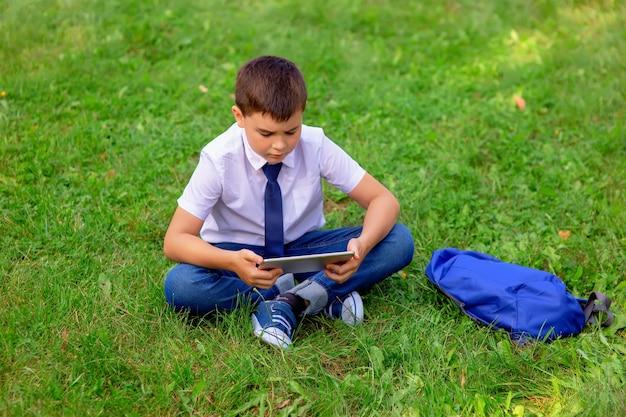 Ernstige schooljongen in een wit overhemd en een blauwe stropdas zit op groen gras tegen een blauwe lucht met witte wolken en kijkt naar een tablet.