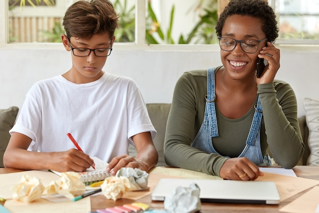 Ernstige schooljongen in wit t-shirt, schrijft records in notitieblok, bezig met studeren