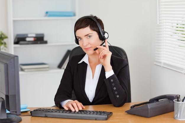 Ernstige secretaresse die met een hoofdtelefoon roept