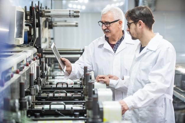 Ernstige senior en jonge kwaliteitsinspecteurs in laboratoriumjassen met behulp van tablet voor analyse van drukpersfouten in drukkerij