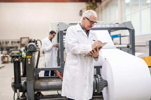 Ernstige senior inspecteur in laboratoriumjas staande op drukpers met papierrol en het maken van aantekeningen op het klembord