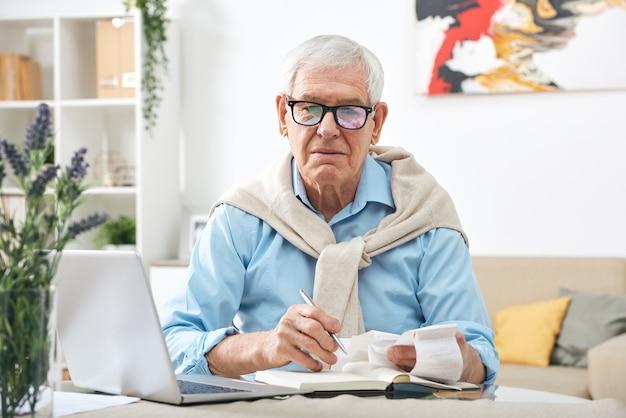 Ernstige senior man in bril kijken via betalingsrekeningen en notities maken in notitieblok zittend aan tafel