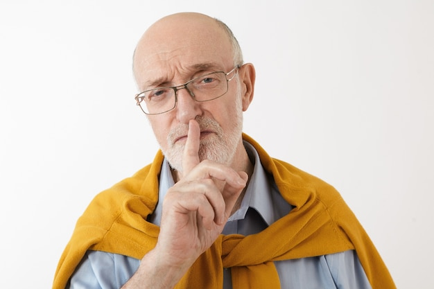 Ernstige senior volwassen man die zijn wijsvinger op zijn lippen plaatst met shhh shushing-teken dat een bril en stijlvolle kleding draagt en vertrouwelijke informatie houdt. gebaren, symbolen, geheim en controle