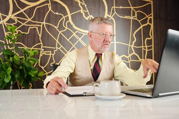 Ernstige senior zakenman contract op laptop scherm lezen en belangrijke details opschrijven