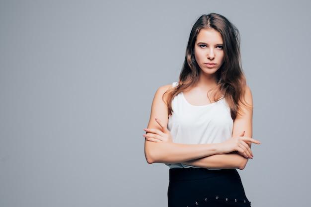 Ernstige sexy meisje in mode moderne kleding is poseren in studio geïsoleerd op een witte achtergrond